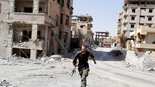 A British volunteer fighter of Syrian Democratic Forces runs for cover to avoid sniper fire of Islamic State militants