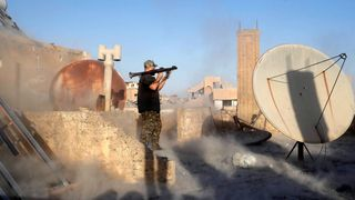 An American volunteer fighter of Syrian Democratic Forces fires an RPG during a battle with Islamic State militants