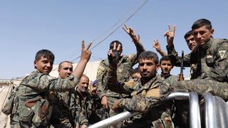 Fighters of the Syrian Democratic Forces gesture  to the media as they ride a truck on the way to the frontline in Raqqa