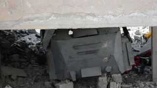 An armoured suicide vehicle of the Islamic State militants under the rubble of a building