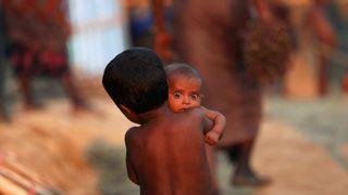 A Rohingya refugee child carries an infant at a refugee camp in Palang Khali near Cox's Bazar, Bangladesh
