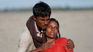 Arif Ullah, whose village was burnt down and relatives killed by Myanmar soldiers, comforts his wife Shakira who collapsed from exhaustion
