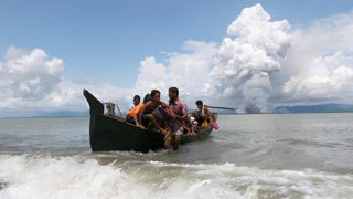 Smoke is seen on Myanmar's side of border as a boat carrying Rohingya refugees arrives to the shore after crossing the Bay of Bengal