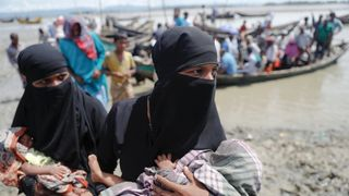 Rohingya refugees who just arrived from Myanmar carry their newborn babies as they make their way to a relief centre in Teknaf