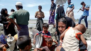 Rohingya refugees who arrived from Myanmar pick up their children and belongings to make their way to a relief centre in Teknaf, near Cox's Bazar in Bangladesh