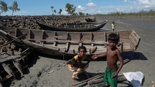 Children collect wood from remnants of some 20 boats that ferried Rohingya refugees fleeing violence in Myanmar