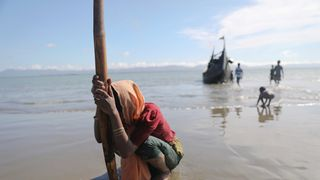 A woman collapses from exhaustion as Rohingya refugees arrive from Myanmar to the shore of Shah Porir Dwip, in Teknaf, near Cox's Bazar in Bangladesh