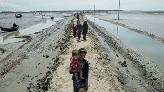 Rohingya Muslim refugees walk towards a camp go in a camp after they crossed the border from Myanmar