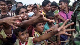 Rohingya boys reach for humanitarian aid as the Bangladesh military keeps things under control