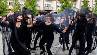 Women perform under black fabric during a street performance in Pristina against sexual harassments in Kosovo