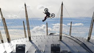 Action sports performer Travis Pastrana somersaults on his motorbike as he jumps between two barges on the River Thames