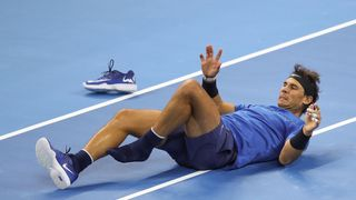 Rafael Nadal falls during his match against Lucas Pouille of France in the Men's singles first round of the China Open in Beijing