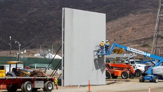People work in San Diego, California, U.S., at the construction site of prototypes for Donald Trump's border wall with Mexico