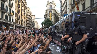 Catalonian police officers surround the 'General Direction of the National Police of Spain' offices  as protesters gather outside in Barcelona