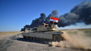 Iraqi army members ride on a tank on the outskirts of Hawija, Iraq