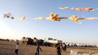 Children fly their kites as they play inside a refugee camp for people displaced by fighting in Ain Issa, Syria