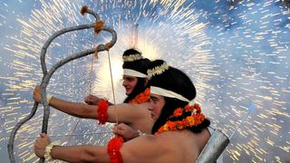 Artists dressed as Hindu gods Rama and Laxman act as fireworks explode during Vijaya Dashmi, or Dussehra festival celebrations in Chandigarh, India