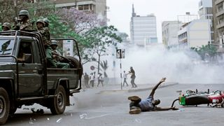 A supporter of Kenyan opposition National Super Alliance coalition is hit by a police truck during a protest along a street in Nairobi, Kenya