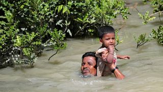 A man holds his child as he swims across the Bangladesh border
