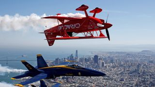 The U.S. Navy Blue Angels flight demonstration squadron and Team Oracle aerobatics pilot, Sean Tucker, fly over San Francisco Bay