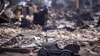 A toy car is left scorched in a neighbourhood destroyed by fire near Cardinal Newman High School in Santa Rosa, California
