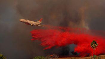 A DC-10 aircraft drops fire retardant on a wind driven wildfire in Orange, California