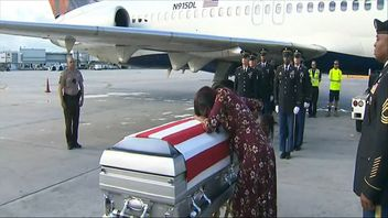 The wife of Sgt La David Johnson weeps on his coffin as his body is returned to Miami