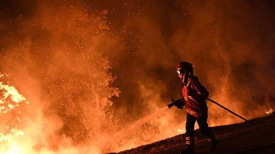 A firefighter tries to extinguish a fire in Cabanoes near Louzan as wildfires continue to rage in Portugal on October 16, 2017
