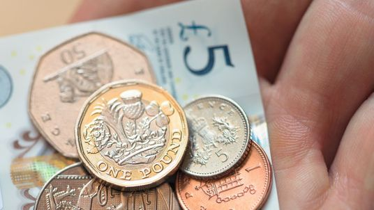 British five pound note and coins - Stock image