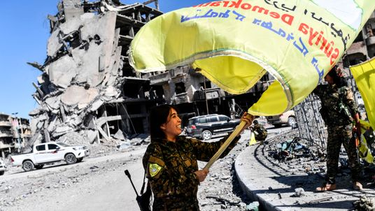 An SDF commander waves her group's flag at Al-Naim square in Raqqa