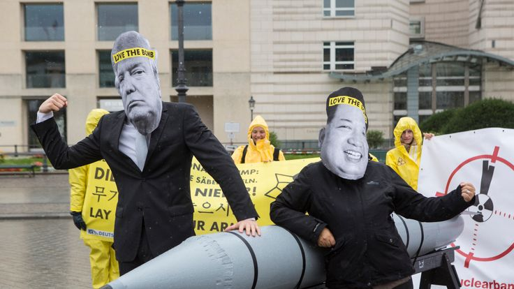 Activists wearing masks to look like US President Donald Trump and North Korean Kim Jong-Un pose next to a Styrofoam effigy of a nuclear bomb while protesting in front of the American Embassy on September 13, 2017 in Berlin, Germany