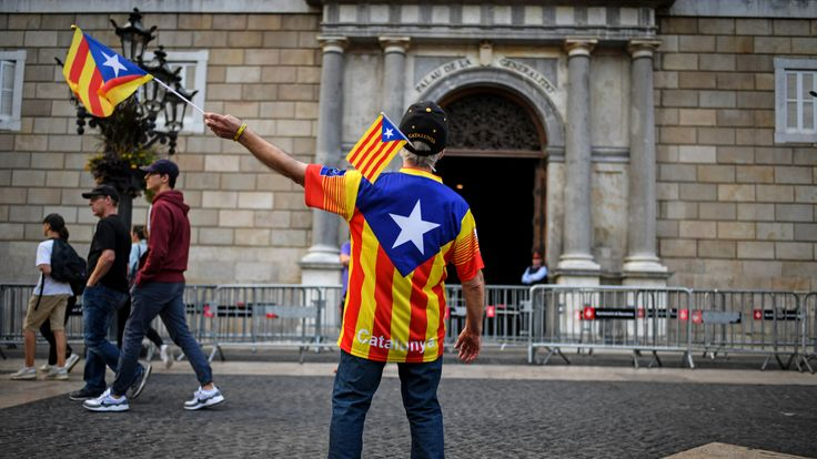 An independence supporter waves a flag outside the Palau Catalan Regional Government Building as Catalonia returns to work following last week's decision by the Catalan parliament to vote to split from Spain, on October 30, 2017 in Barcelona, Spain