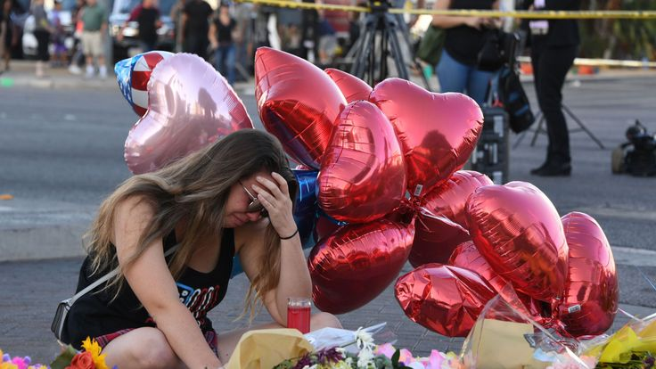 Destiny Alvers who attended the Route 91 country music festival and helped rescue her friend who was shot, reacts at a makeshift memorial on the Las Vegas Strip in Las Vegas, Nevada on October 3, 2017