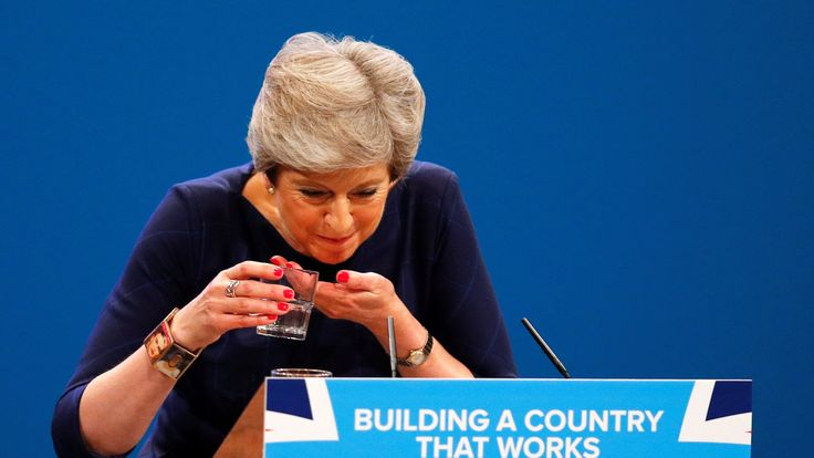 Theresa May struggles with her glass of water after suffering a coughing fit whilst addressing the Conservative Party conference