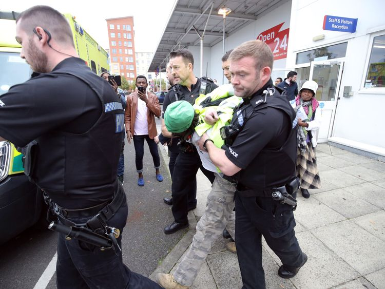 Adam Jammeh is led away from a Tesco store after the former security worker staged a protest
