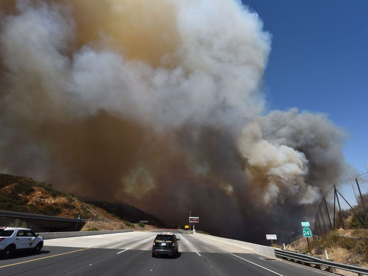 A police car blocks the 241 freeway as smoke from the Canyon 2 Fire covers the freeway near Orange, California, October 9, 2017 in Orange, California