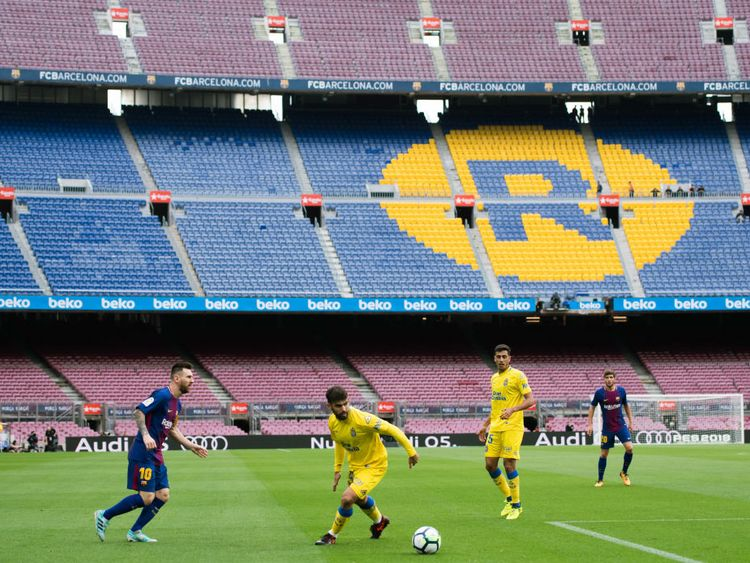 Lionel Messi plays the ball in front of an empty Nou Camp after a decision was made to play behind closed doors