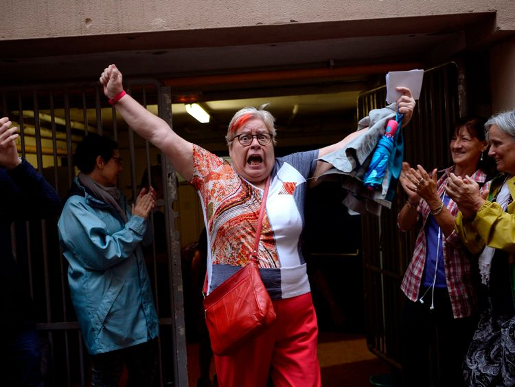 A woman celebrates outside a polling station after casting her vote in Barcelona