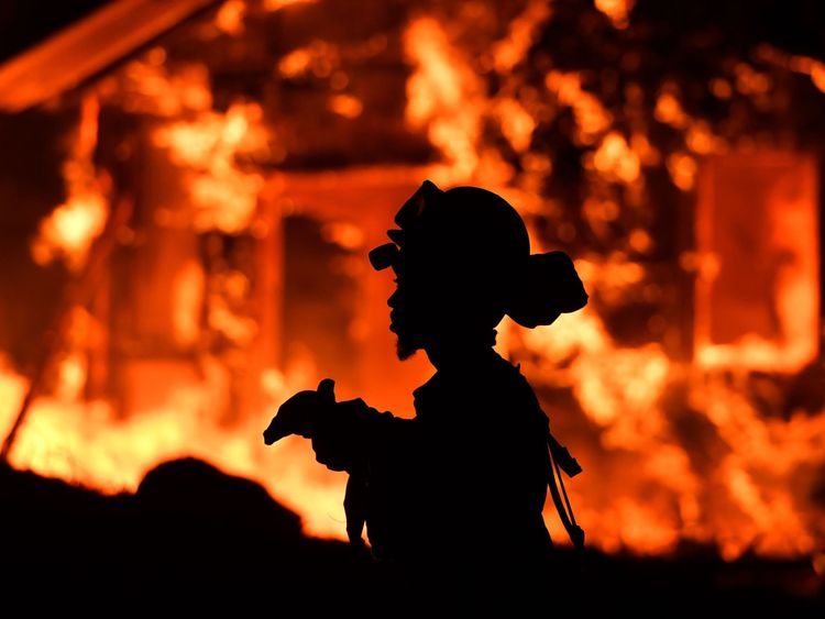 An inmate firefighter monitors flames as a house burns in the Napa wine region in California on October 9, 2017, as multiple wind-driven fires continue to whip through the region