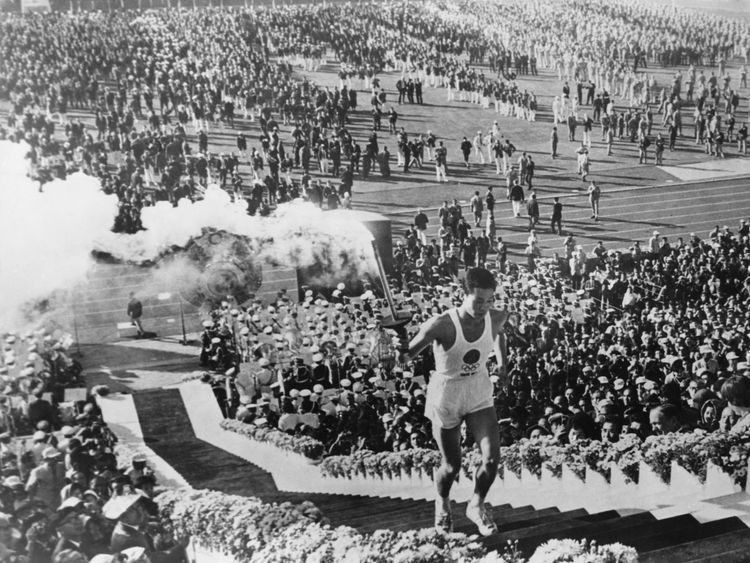Olympic flame torchbearer Yoshinori Sakai mounts the steps to light the cauldron at the opening ceremony of the Summer Olympic Games at the National Olympic Stadium, Tokyo, 10th October 1964