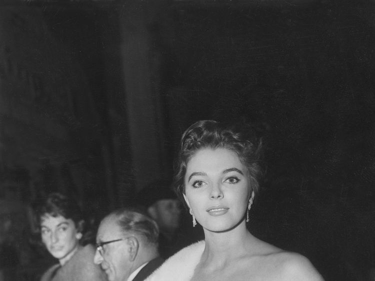 2th Sep 1956: Joan Collins arrives during a European premiere of The King  I, wearing an dusk robe and white fur stole. (Photo by Keystone/Getty Images)