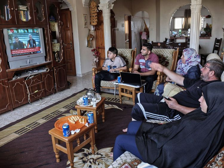 Palestinians watch footage of the agreement on television