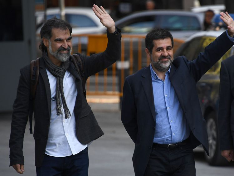 Catalan National Assembly (ANC) president Jordi Sanchez (C), and Pro-independence Catalan Omnium cultural language association president Jordi Cuixart (L), who are under investigation for sedition, wave as they arrive at the High Court in Madrid on October 16, 2017. / AFP PHOTO / GABRIEL BOUYS (Photo credit should read GABRIEL BOUYS/AFP/Getty Images)