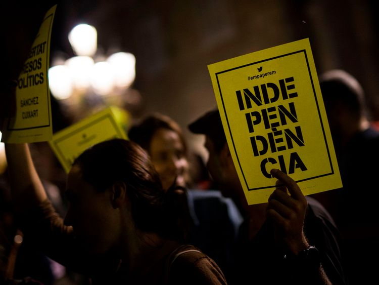 A man holds a paper reading in Catalan 'Independence' in front of the Generalitat Palace on October 17, 2017 in Barcelona. The demonstrators protested the judicial decision to imprison Spanish president of the Omnium Cultural, Jordi Cuixart, and Spanish president of the Catalan National Assembly (ANC), Jordi Sanchez. / AFP PHOTO / PAU BARRENA (Photo credit should read PAU BARRENA/AFP/Getty Images)