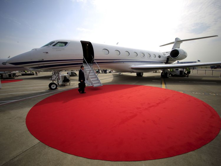 A man walks on a red carpet in front of the Gulfstream G650 ER jet