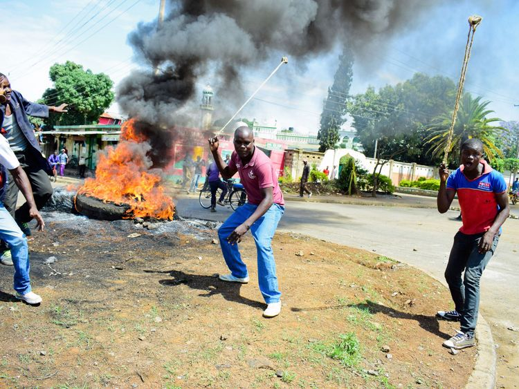 Supporters of Mr Odinga prepare to throw stones as they demonstrate in Kisumu
