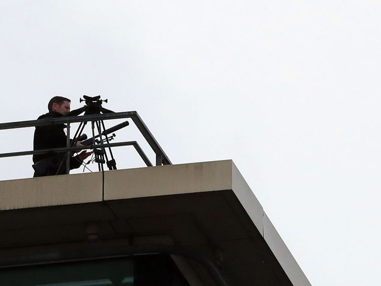 Police marksmen wait on a roof above the conference centre
