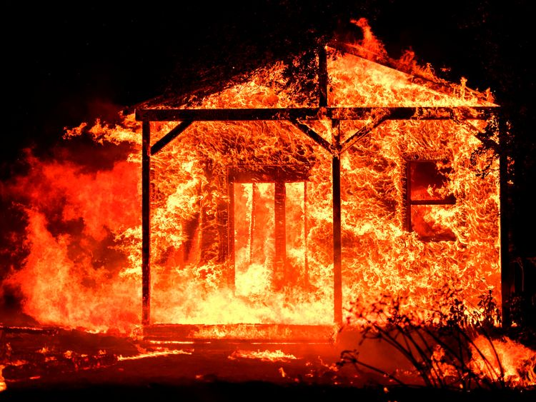 Flames overtake a structure as nearby homes burn in the Napa wine region in California on October 9, 2017, as multiple wind-driven fires continue to whip through the region