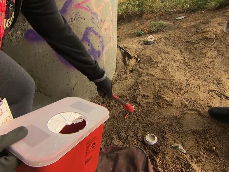 A worker picks up a discarded syringe