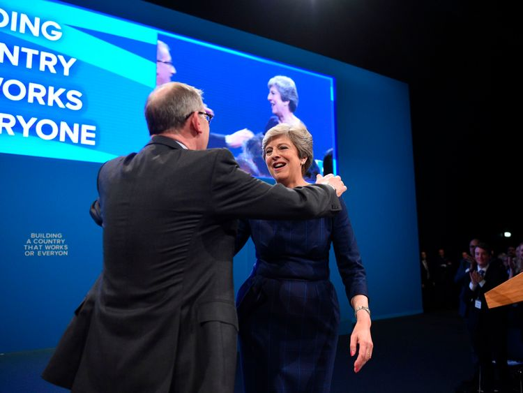 Britain's Prime Minister Theresa May (R) is hugged by her husband Philip May (L) on the stage at the end of her speech on the final day of the Conservative Party annual conference at the Manchester Central Convention Centre in Manchester, northwest England, on October 4, 2017